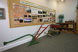 The Impact of Agriculture on the Economy of Manatee County exhibit, John Deere Plow in the forefront, and a seeder behind the blow. A general store scale can be seen on the counter in the back of the picture.