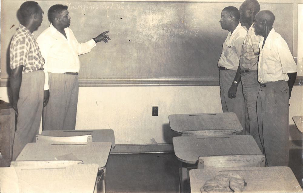Five men stand at the front of a class room in front of a chalkboard with empty desks visible