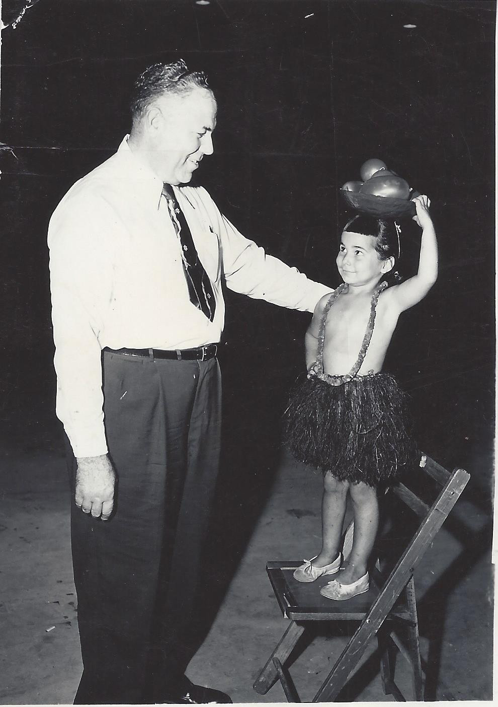 "man in dress pants and tie on left ""Anthony Rossi"" little girl on chair wearing grass skirt, flower necklace, and braided pigtails with a bowl of oranges on her head ""Christine Keston Pool"""