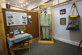 Citrus Room exhibits featuring the Tropicana Suit in the center of the picture, a citrus picking bag to the right. On the left a panel about Atwood Grove and juicing tools on the table.