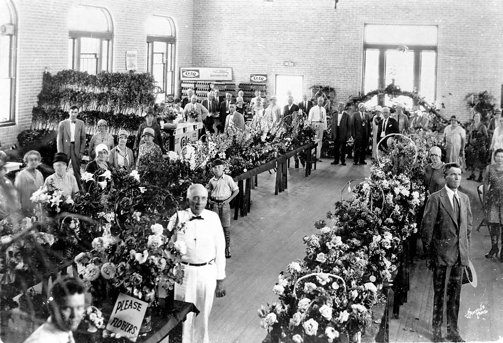 Large room filled with displays of lower arrangements, celery bunches, and Celo soda in the back left corner. People pose stiffly around the room for photo