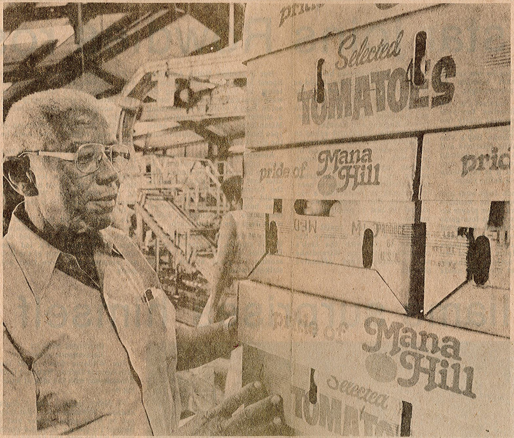man stands next to stacked boxes of tomatoes