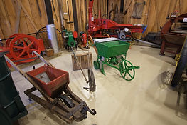 Interior of the Barn Room. Seeders can be seen in the middle of the room. Galloway Engine is visible on the far right hand side. In the middle of the back a Silo Filler is visible on the far left is a Fanning Mill.