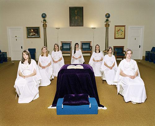 Imagem composta por 7 meninas, sentadas em semicírculo, viradas para frente, com uma Bíblia aberta repousada em um altar no centro.