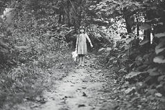 little girl standing in the middle of a wooded path