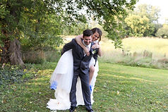 bride and groom laughing while groom carries bride on his back