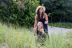 mother and daughter laughing while standing in the beach grass