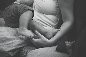 moter holds baby's foot as she cradles him in her arms