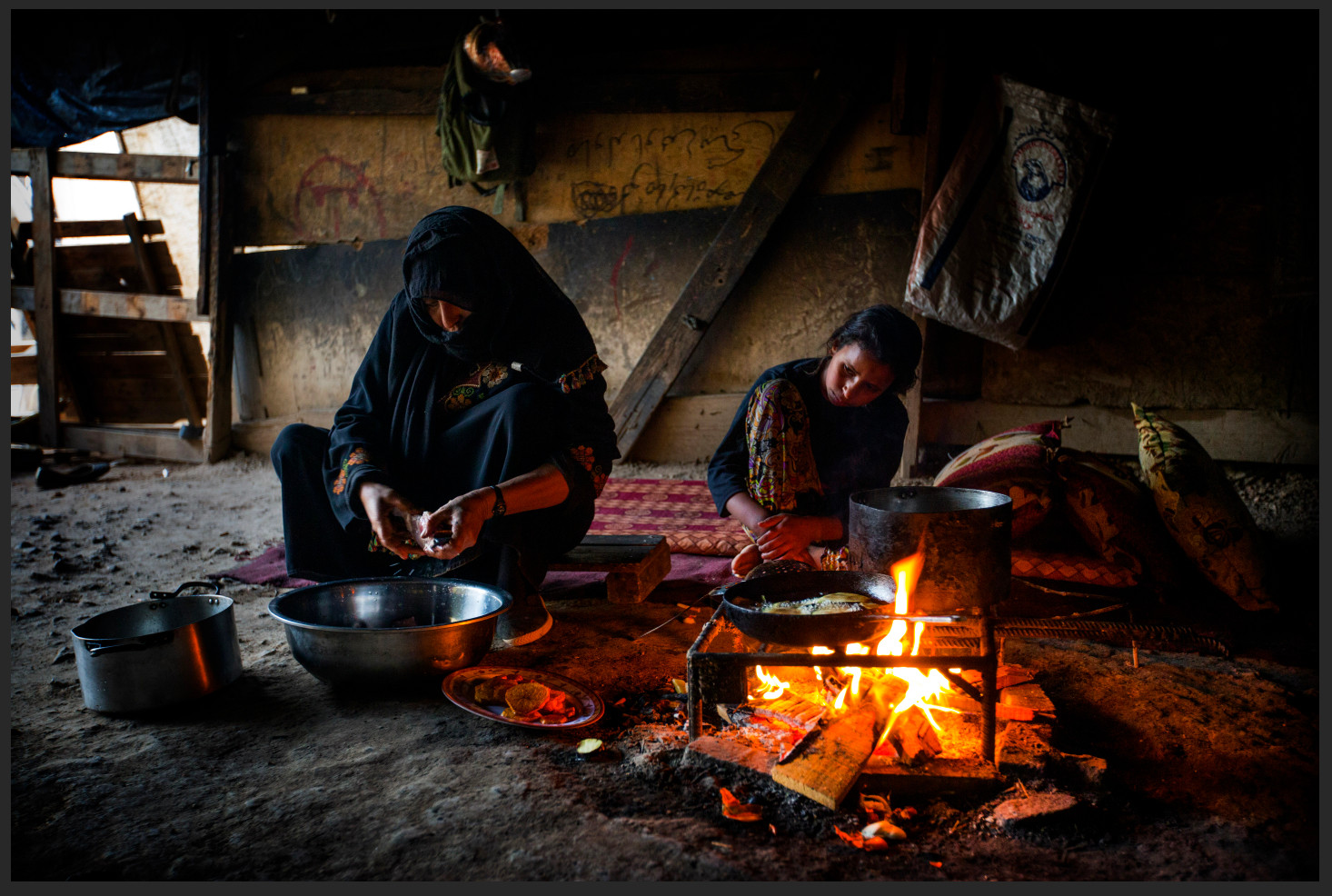 Nasrin looks on as her mother, Sara Dahouk, prepares a meal for the family in the tent-like structure where they live.