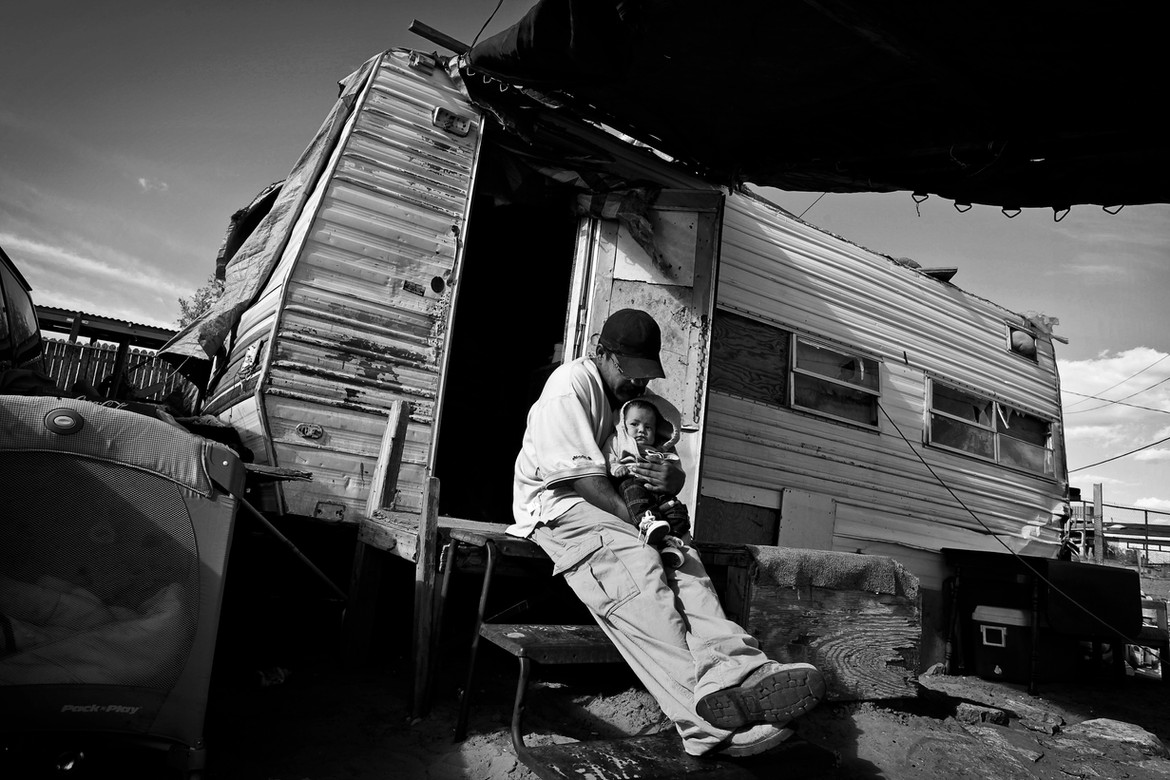 Eddie Zepeda sings to his newborn son outside the She and six of her children now live in a sagging travel trailer without water or electricity. dilapidated trailer he shares with his partner and 5 other children. The trailer leaks, is filled with mold and is causing the children