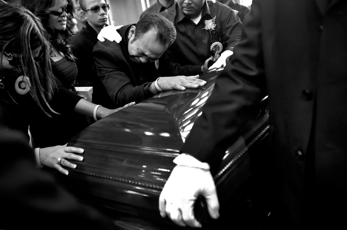 """Melody Ross's  father, Vannaret, throws himself onto his daughter's coffin as pallbearers look on. Racked by pain and disbelief, Melody's family and friends struggle to make sense of the sixteen year old being killed by a stray bullet fired by a gangmember. """"Every kid our age -- we don't ever think we're going to die,"""" said Dylan Vassberg ,who shared a chemistry class with Melody. """"We never think that. We think we're going to college and we're going to have a long life and die of old age. Not die because someone decided to shoot a gun."""""""