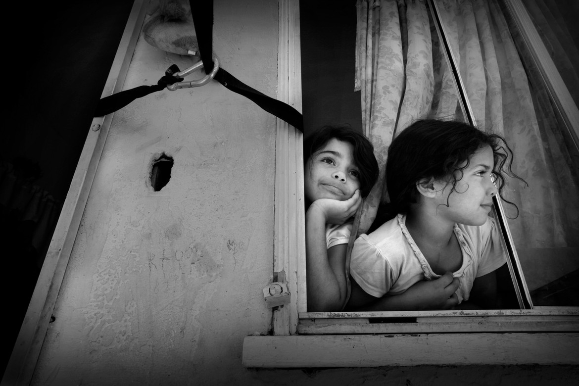 Josue's sisters Kimberlin, left, and Katherine peer out the window of their Long Beach home. Their mother has tried to discourage all of the children from playing outside since the shooting.