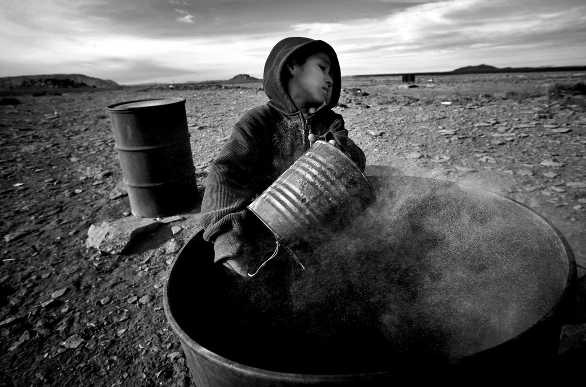 Taking over from his father who passed away 2 months ago, six-year-old, Zeke Whiterock, empties a can of ash near their dilapidated trailer in Cameron, Az. On this densely populated Reservation, children grow up fast under the harsh living conditions.