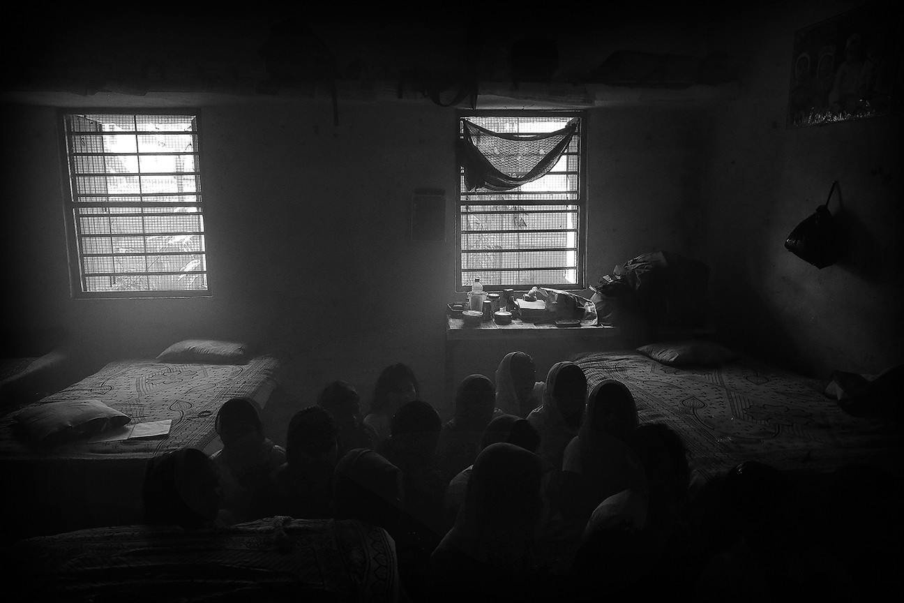 The girls pray together inside their communal bedroom that sleeps 20 during the five holy days of Durga Puja.