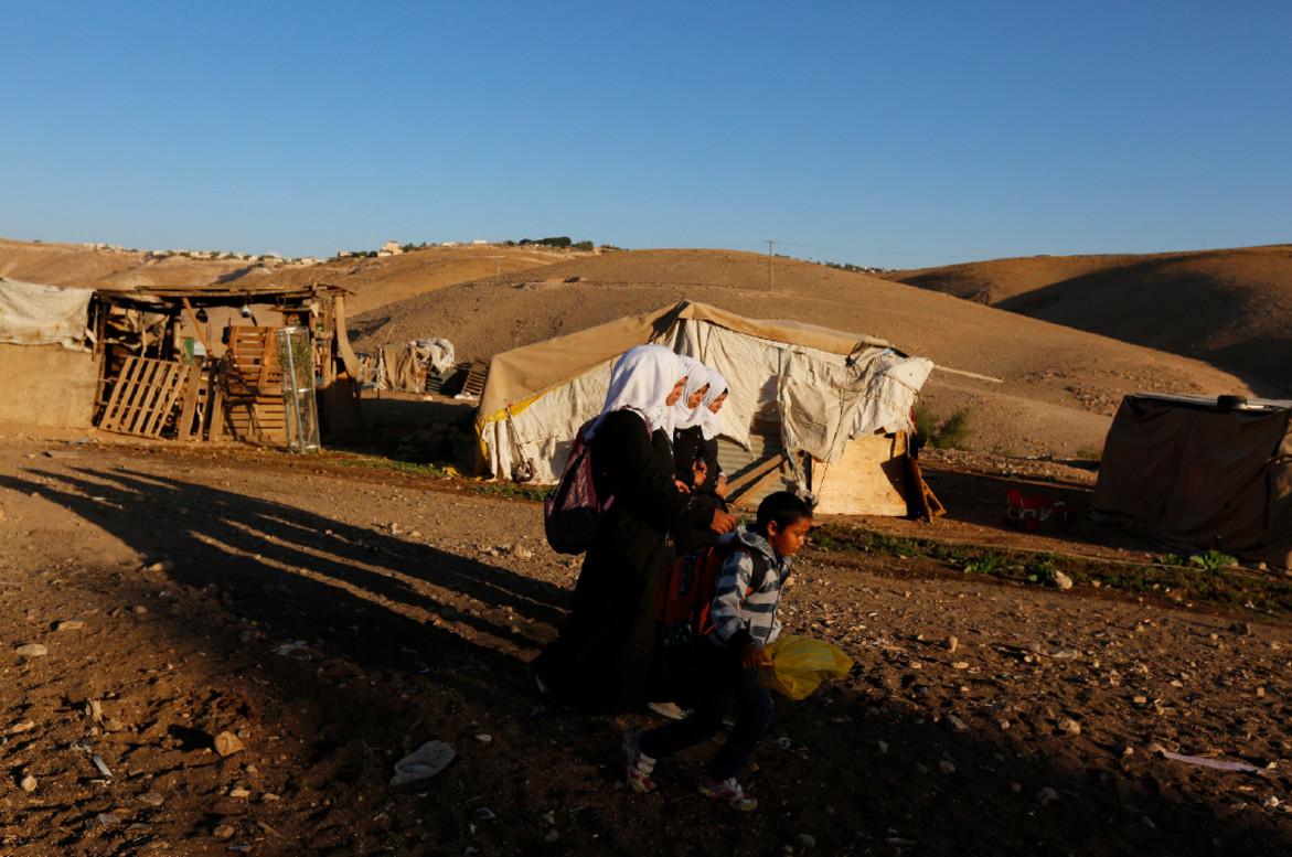 As the sun rises over the desert valley, uniformed schoolchildren walk to class.