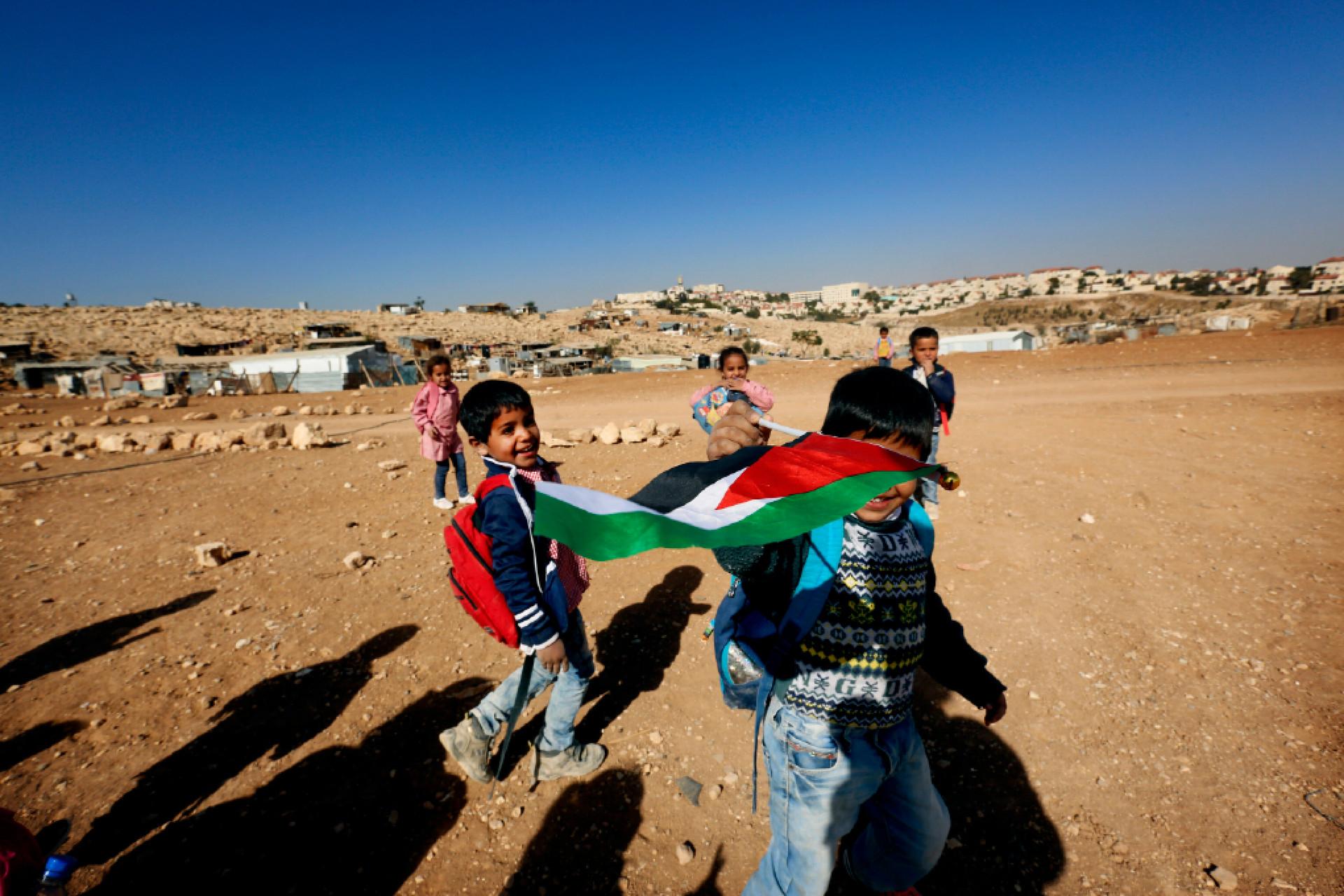 Bedouin schoolchildren run with a Palestinian flag after attending school near their home.