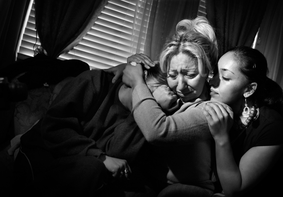 """Family members console one another after the shooting death of 14-year-old Eduardo Rodriguez. From left, his mother, Angelica Rojos; aunt, Martha Rojas; and cousin, Mireya Tejeda, embrace at Rojos' Long Beach home last month.  Rodriguez was playing video games when he heard a knock at the door. As he went to answer it, gunmen fired through the screen door. Rodriguez stumbled into his parents' bedroom and said, """"Dad, I can't breathe."""" He collapsed in his father's arms. According to police, Rodriguez's older brother may have been embroiled in a dispute with gang members."""