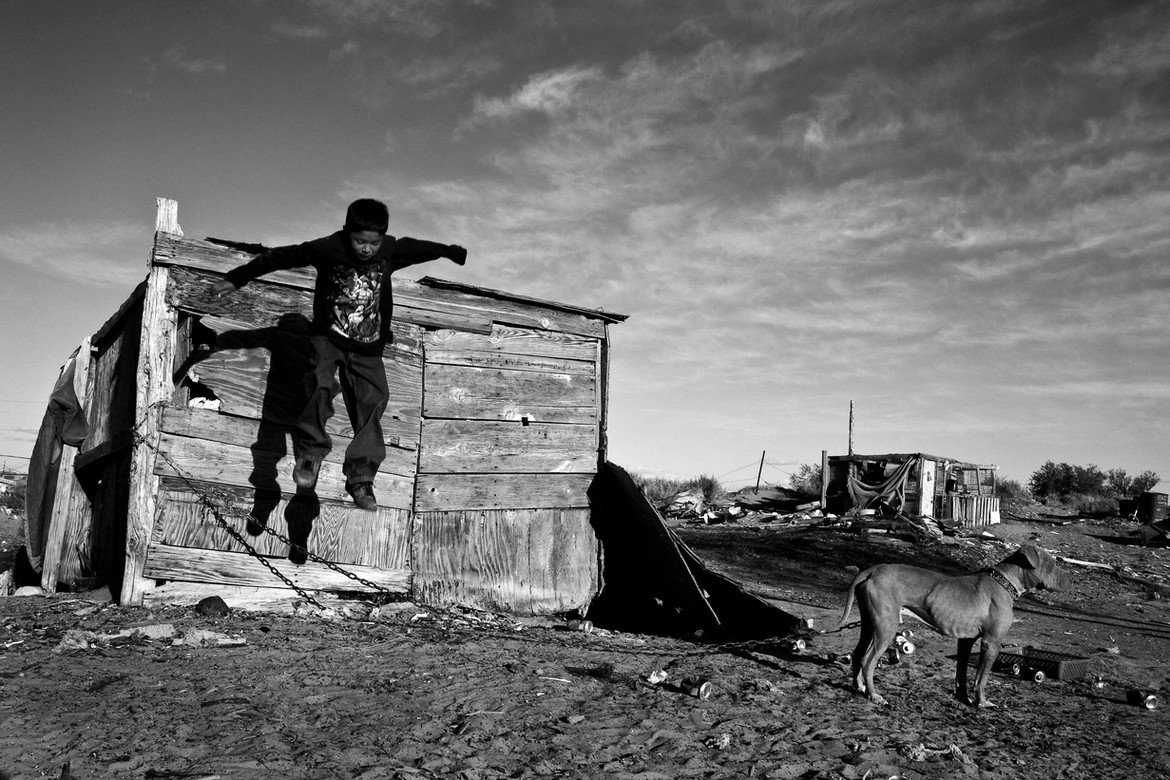 Julio Almeida, 8, jumps off one of the rickety shacks that litter the backyard where he lives. Many say they didn't understand the details of the Freeze and didn't know its boundaries. Some people, including the Almeida family, who lives not far from Tuba City, don't even know whether or not they live on the Freeze.