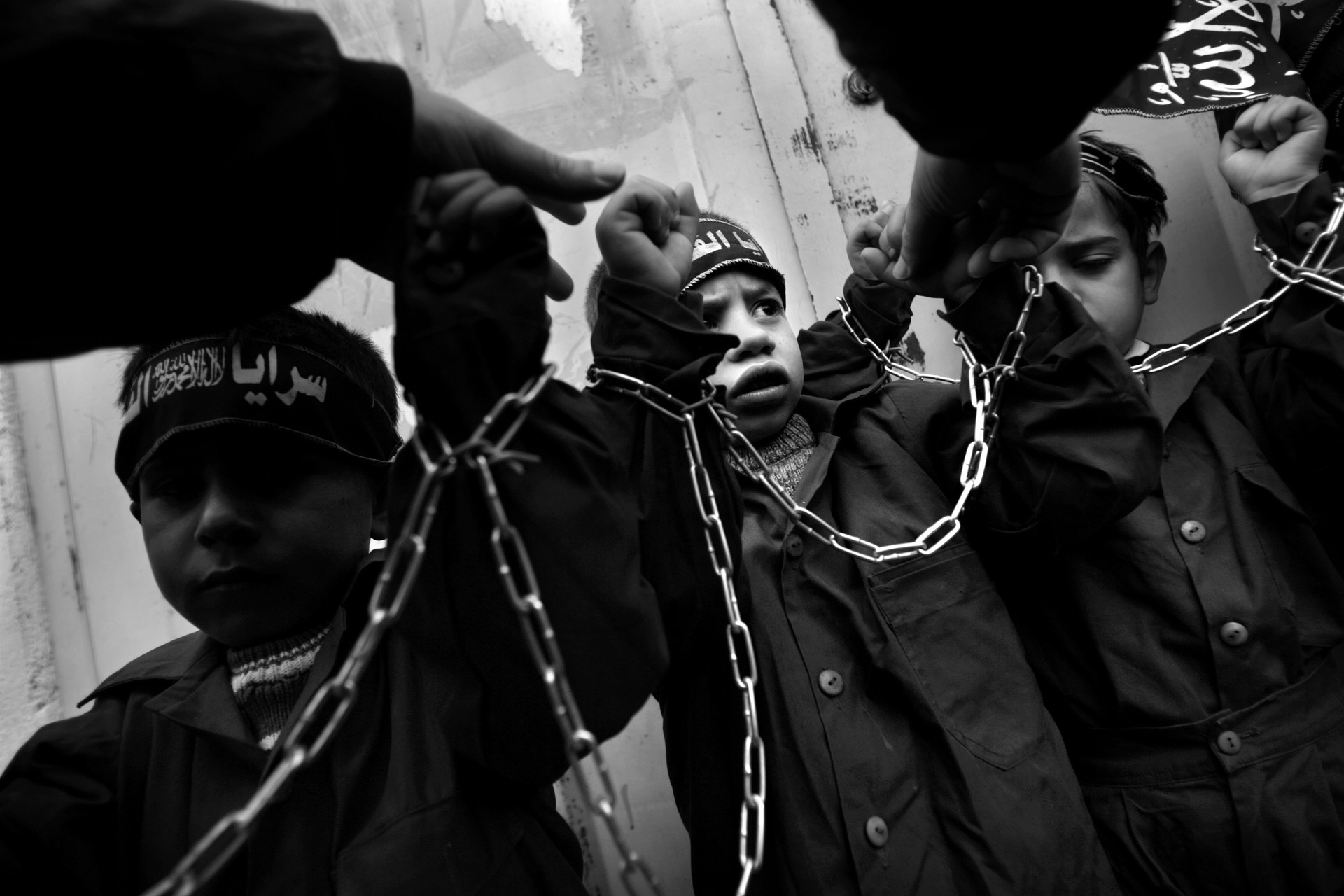 In a conflict which has claimed hundreds of  young people – Israeli and Palestinian – injury and death become the stuff of child's play.  Here, Palestinian children, shackled in chains at a Hamas rally, are used as cultural propaganda for Hamas.