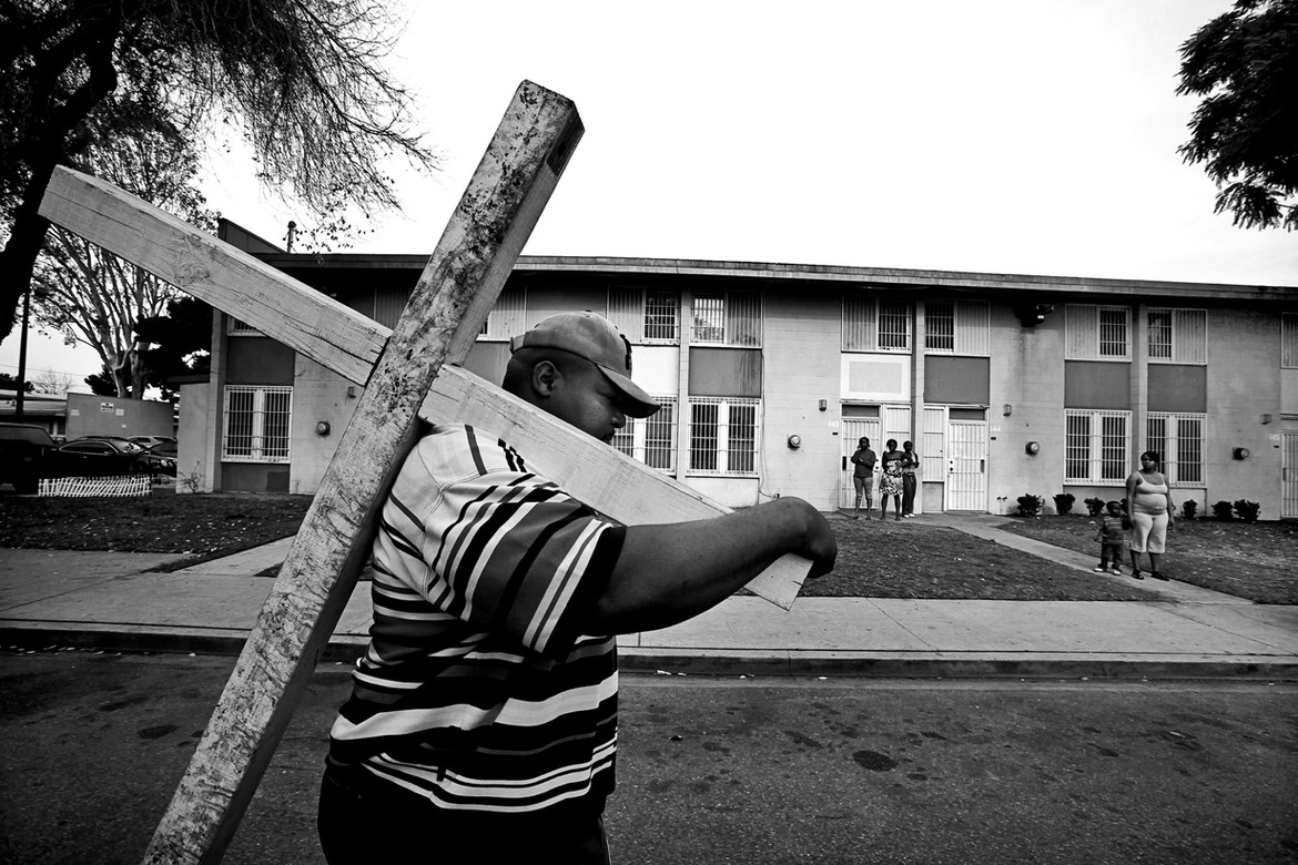 Pastor Wyman Jones, of Sweet Hill Baptist Church in South Los Angeles,  carries a wooden cross through the Nickerson Gardens public housing complex to protest gang violence.  Police have said the recent violence was linked to a civil war of sorts within the Bounty Hunters, for years the dominant gang in Nickerson Gardens, apparently over drug sales.