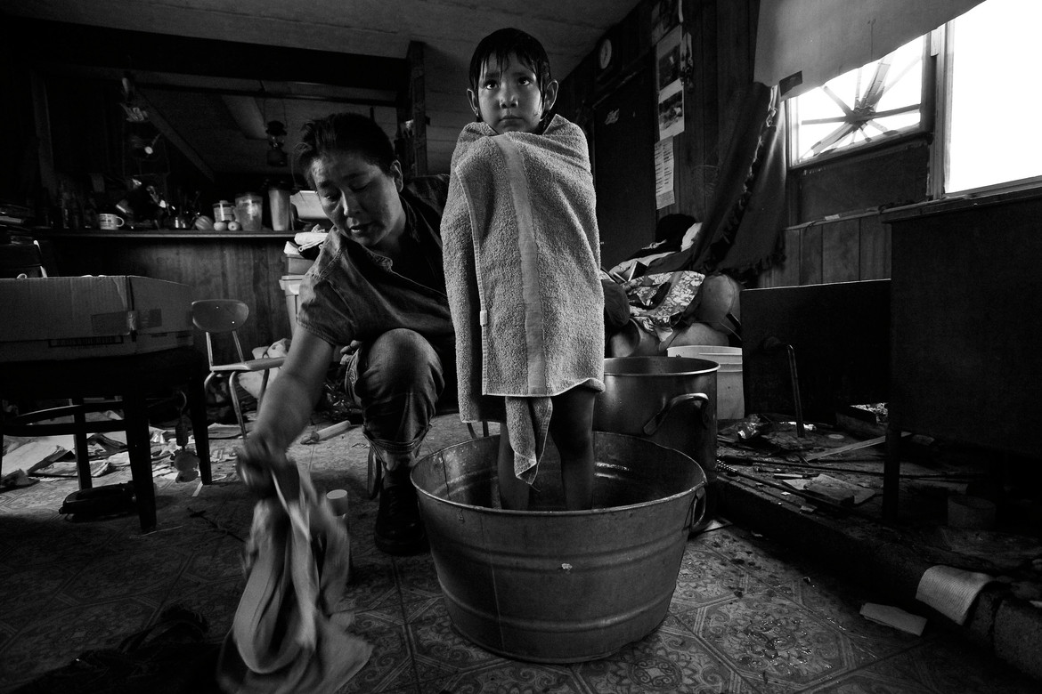 """Thomasina Nez, 35, gives Bobbi, 4, one of her seven children, a bath in a small tin basin next to the wood stove in their dilapidated trailer in Cameron, Arizona, on a wintry day in mid-December. Thomasina, who lives in the now former """"Bennett Freeze"""" area, has no running water and is forced to bathe her children with water hauled from 30 miles away and warmed up by the families' wood stove. She bathes the smallest one, who uses the least amount of water, first, then adds a bit more water to bathe the next in line, and does so until the basin is filled to bathe the 6 year-old. It's too expensive, at 2$ per shower, at the local RV station, to shower her family there. So they go without."""