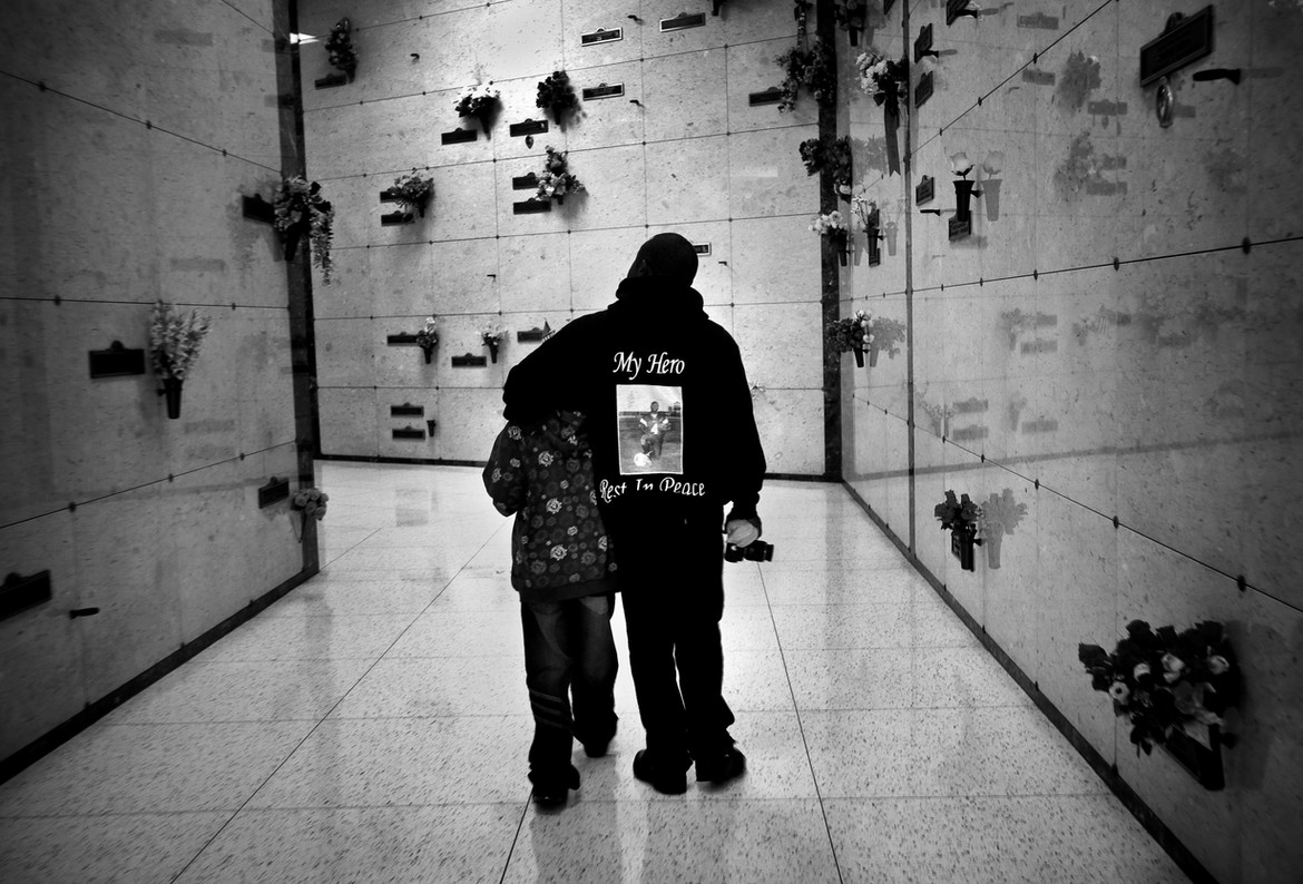 """During a visit to mark Jas' 18th birthday, Jamiel Sr. and Jas' brother, Thomas, walk through the solemn halls of Inglewood Park Cemetery. Said Jamiel Shaw Sr. """"I think my weakness is crying all the time thinking about him. …You can't be the same person anymore because Jas is what made me whole.""""  Army Sgt. Anita Shaw, Jas's Mother, adds, """"When I was serving in Iraq…and I found out my son was murdered three doors from his house in Los Angeles, I was very upset. I was like, how can that be? The United States is supposed to be the safest place, especially for a child."""""""