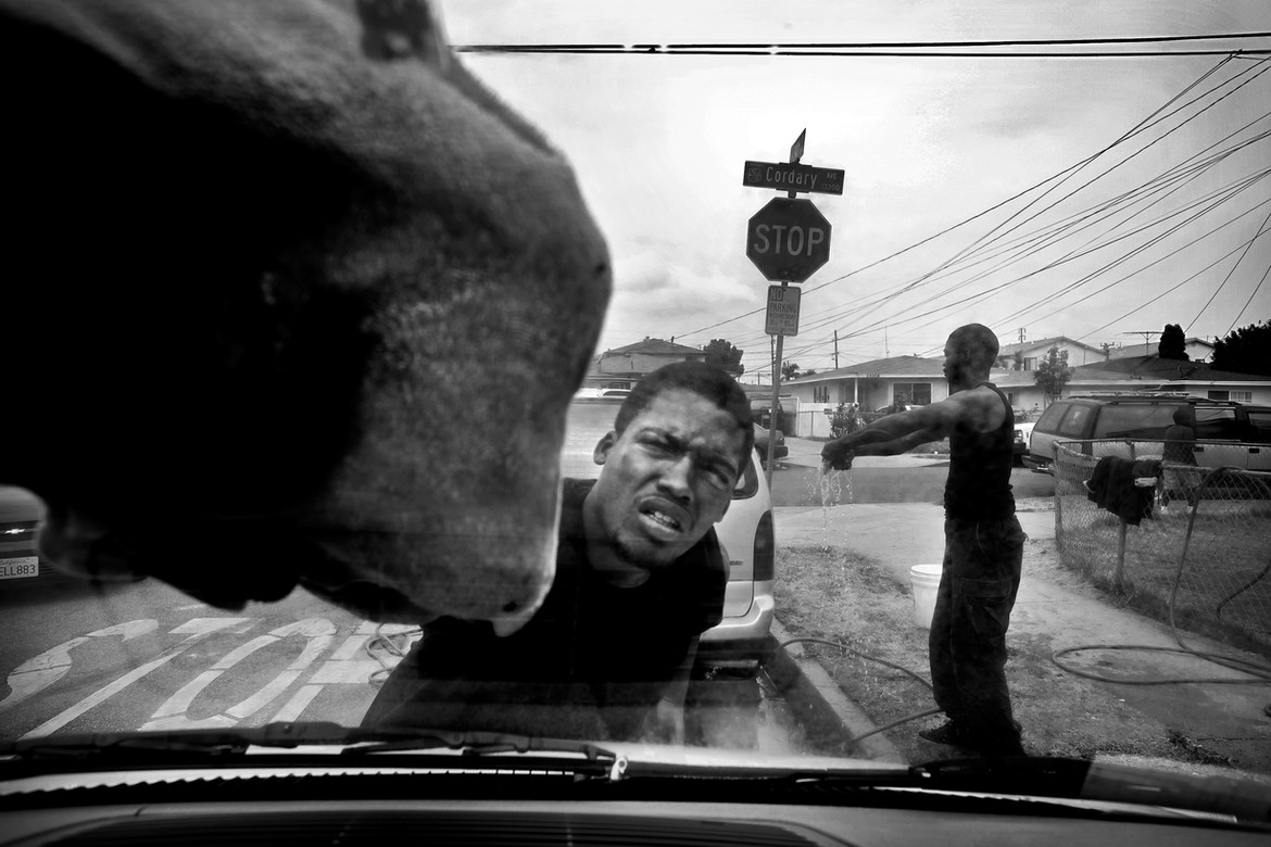 """Edward Cobbin Jr. washes a car at a fundraiser for his brother's burial.  Edwin's body stayed in the morgue for weeks as his family searched for a grave site they could afford.  They settled on an above-ground burial in Compton.  """"We wanted him in the ground, not in the wall … but we didn't have the money,"""" Glee said."""