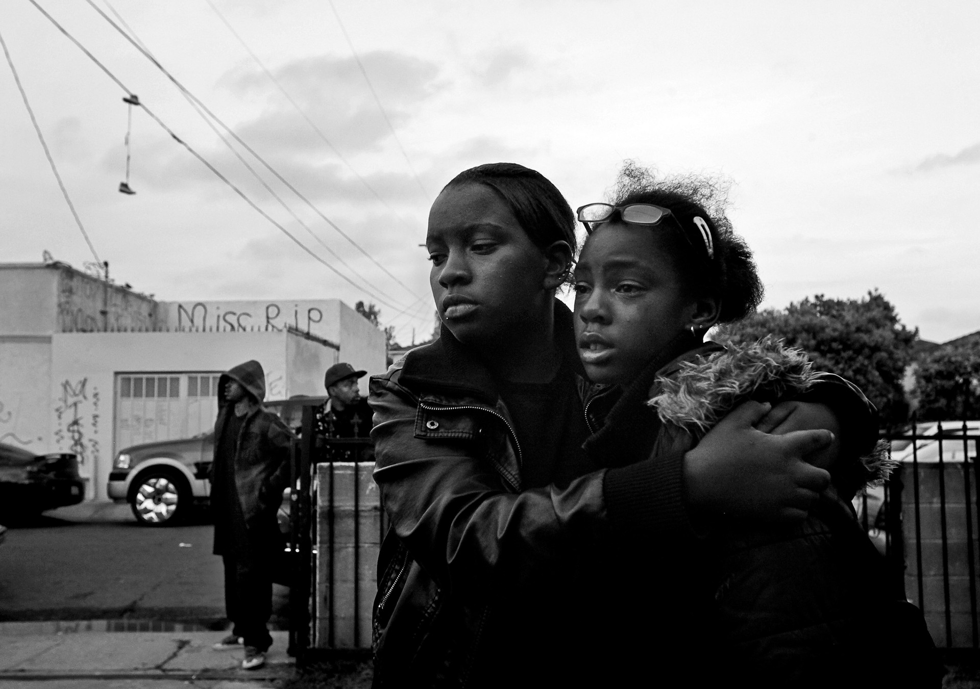Two friends, Keyshae, left, and Ahvriel, embrace in front of the home where 21-year-old Miss Welch was shot and killed in Compton, CA.  Welch had been sitting on the porch with several friends when a gang member approached from the street and opened fire. Welch was struck in the chest, staggered into the living room and collapsed in her mother's arms. Authorities have confirmed that Welch was not a gang member.
