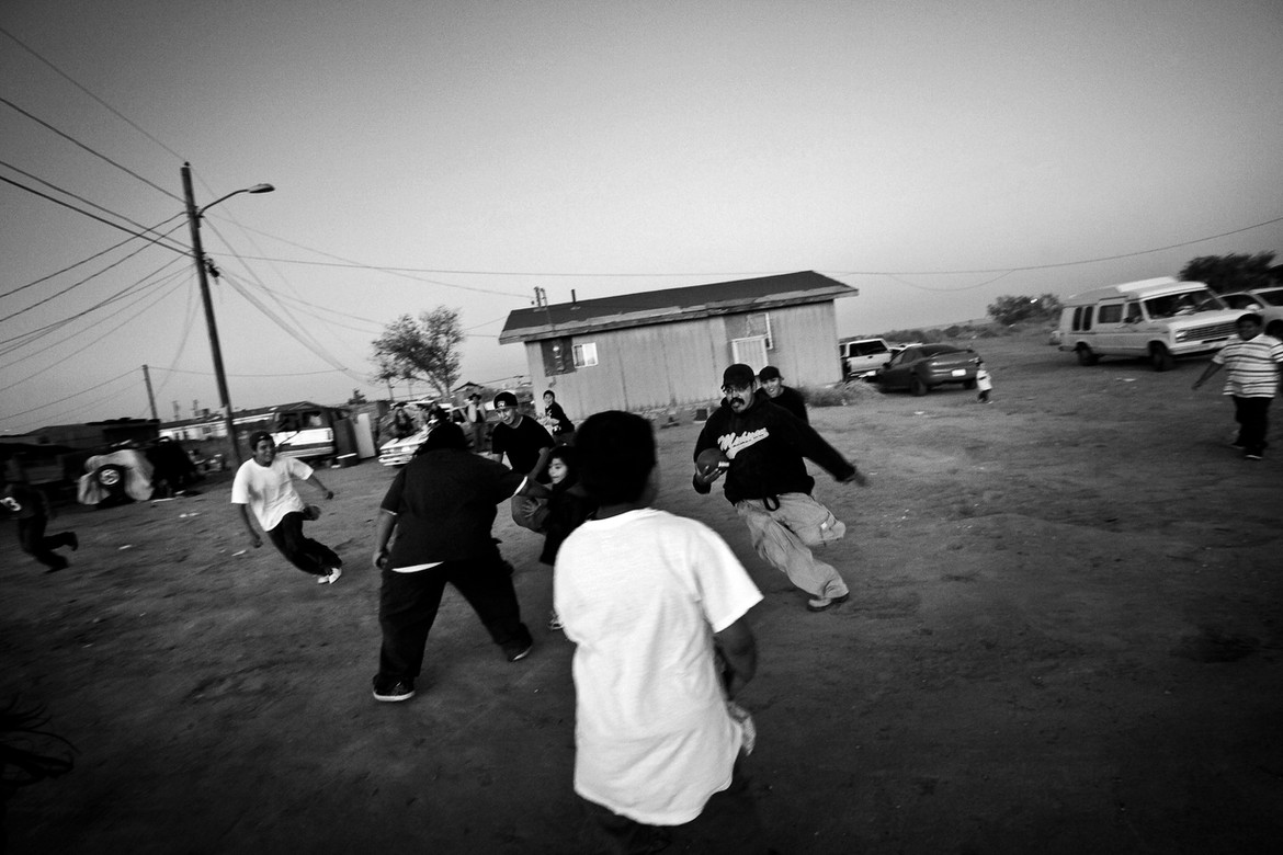 The Navajo say their families keep them together in the hard times. Here, during a birthday visit, the extended family plays a game of football on the dusty ground in front of their home.