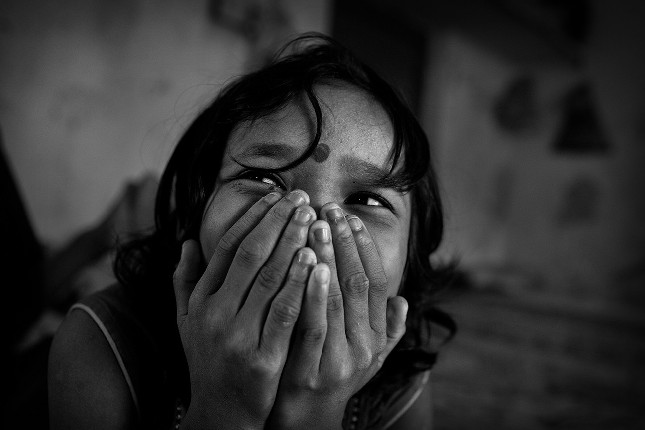 Twelve-year-old Karishma enjoys a shy moment laughing with her friends inside the boarding school where she live with some other 100 girls.