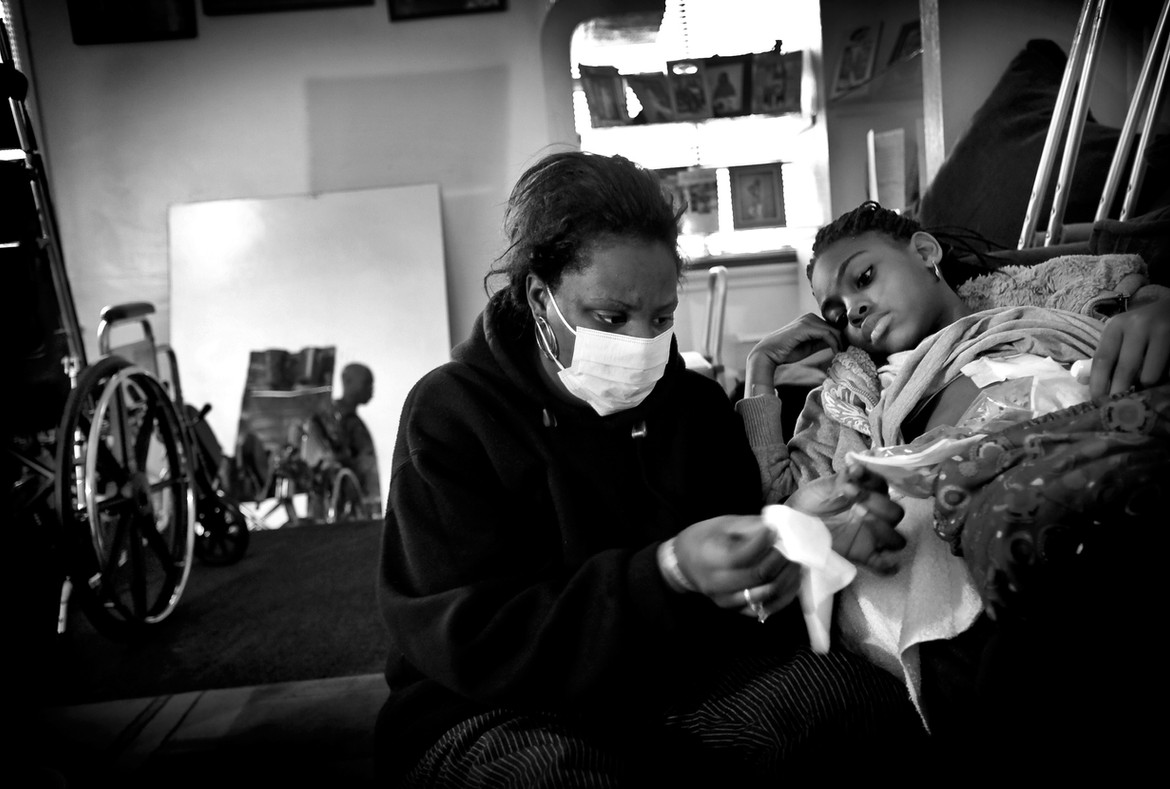 """At the hospital, Erica underwent surgery on her large intestine, where one of the bullets had lodged. The operation was successful, although it left her with a colostomy bag taped to her abdomen. Now Erica's Mother, Shameka, has to adjust to all of her daughters medical needs. Here she changes her daughters colostomy bag on the living room couch """"this is the first time I have ever had to do something like this...I don't know how I'm going to get trough all of this."""" She said while changing Erica's bag. """"I just felt that it should have been me instead of my kid,"""" Harris said. """"I just felt that she didn't deserve it, and to see her in the hospital, seeing her in bed, to see her at her weakest, it was hard."""""""