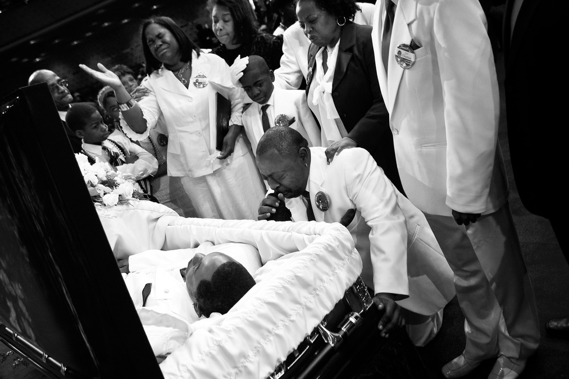 """Jamiel Shaw Sr. kneels before Jas' coffin during funeral services. Standing, from left, are Jas' mother, Anita Shaw; his brother, Thomas; and aunt Althea Shaw. """"To see my son lying there dead…in a casket…to be shot, slaughtered like a dog…it makes you want to go out there and just round up everybody that's in a gang and makes you want to be a crime fighter.""""  On the same day as Jas' funeral, 19-year-old Pedro Espinoza was formally charged in the teen's slaying."""