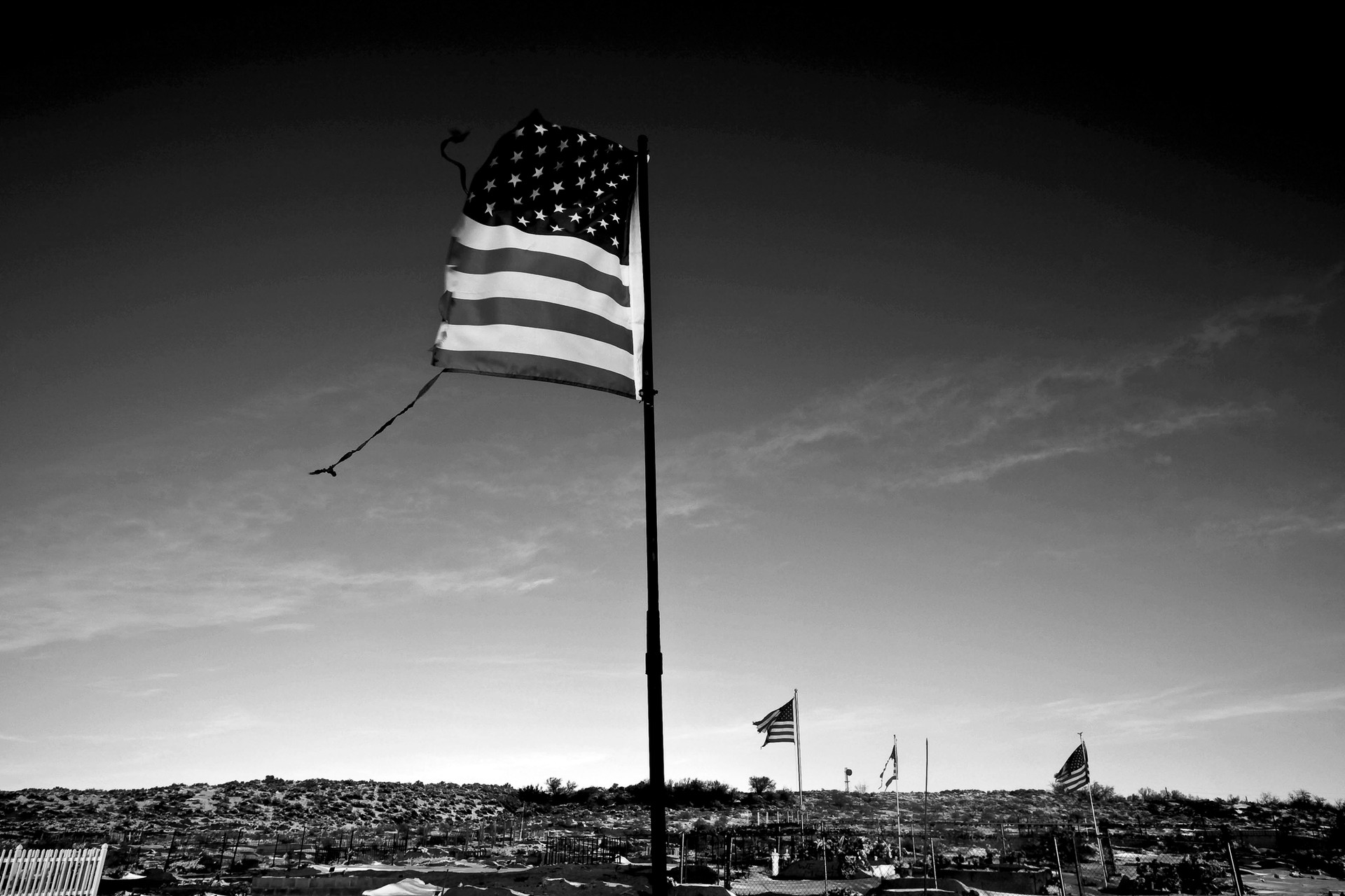 """A torn American Flag flies over a snow-covered cemetery in Tuba, Arizona where Thomasina Nez's former partner, and Father to 5 of her children, is buried. Dispute over the 1.6 million acre tract of tribal land in northern Arizona became known as the """"Bennett freeze."""" It is a land frozen in time because of government bureaucracy."""