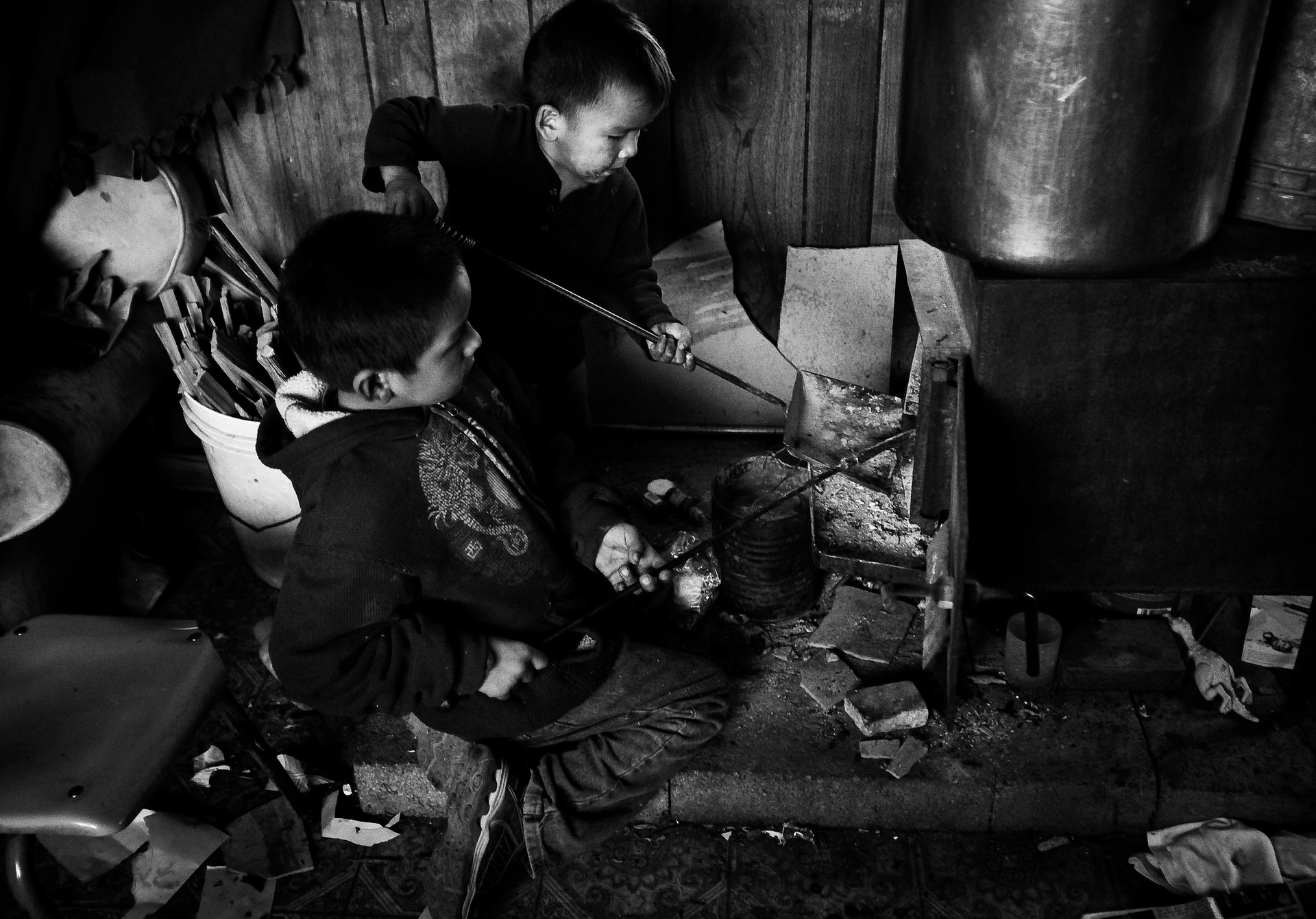 Ashkii Nez Whiterock, 2, and his older brother, Zeke Whiterock, 6, remove ash and add logs to the wood stove in the families trailer in Cameron, Arizona. The family lives in the former Bennett Freeze area without water or electricity and relies on the wood stove to keep the trailer warm during the winter. The wood is cut down in the forest and hauled from some 30 miles away and is costly for the family. Because the children's fatter died two months ago, now Zeke, 6, takes on the tradition of tending to the fire for the family, a chore he used to watch his Father do.