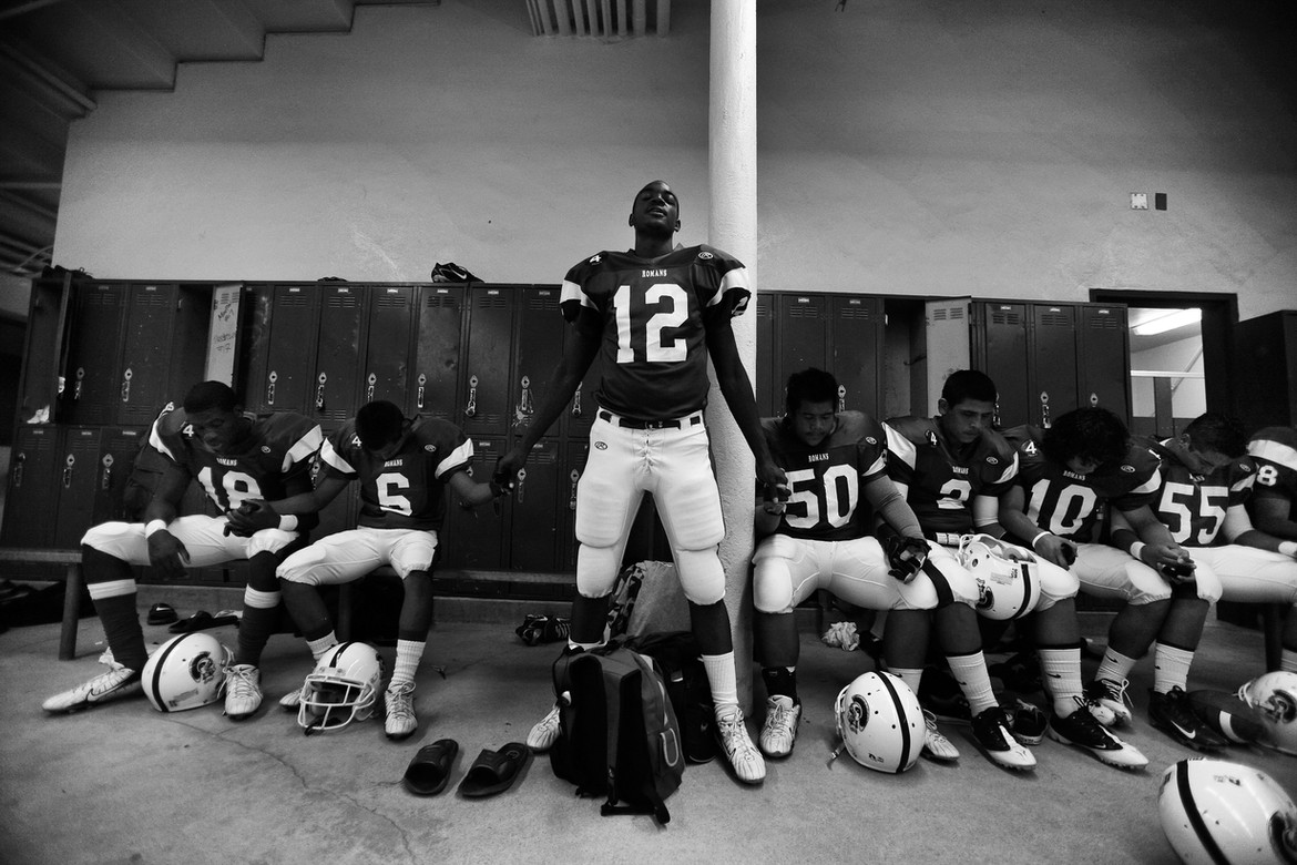 """Je'Don Lasley, a junior receiver at Los Angeles High, chokes up as he delivers a pre-game prayer in the Romans' locker room in the team's first home game since Jas was killed. Jas used to lead the prayers. """"I say whatever comes and hope we're all right,"""" Lasley said. The team's coach, Hardy Williams, said athletes used to be largely excluded from gang violence. Yet his team almost lost a second player, Orlando Isles, who was struck in the right calf in a drive-by shooting. A friend standing next to him, Chris Taylor, died after being shot twice in the head. """"At one time athletes were looked at as pretty prominent, even on the high school level,"""" Williams said. """"Gang members now, maybe it's like a notch in their belt or something."""""""