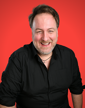 Portrait of Mitch smiling, wearing a black shirt, with a link to contact page, against a red background