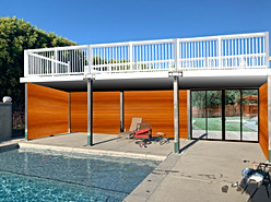 Pool deck area rendered to clients idea. Wooden back wall with a sliding door and an upper sun deck that is safe for children.
