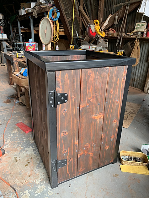 Finished trash can cover with swinging door.