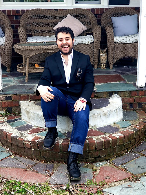 Composer and musician Nebal Maysaud laughing while seated on the edge of their porch