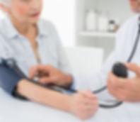 Doctor que toma la presión arterial del paciente anciano