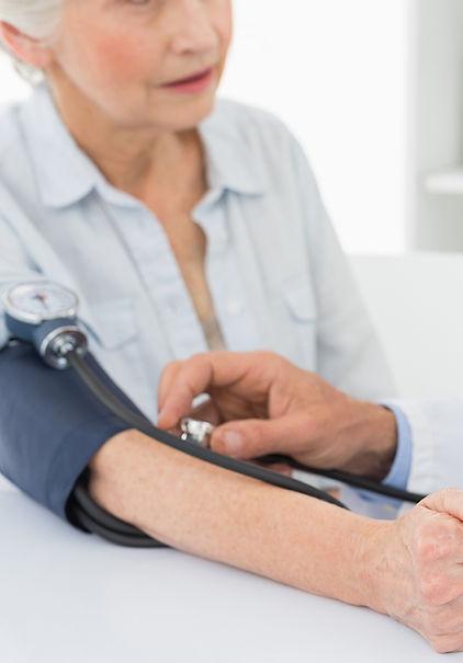 Doutor que toma a pressão sanguínea do paciente idoso