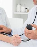 Доктор принимая кровяное давление пожилы