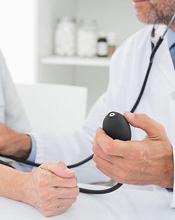Doutor que toma a pressão sanguínea do p