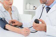 doctor taking blood pressure of adult