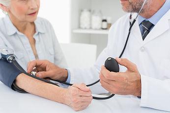 Doctor taking blood pressure of older pa
