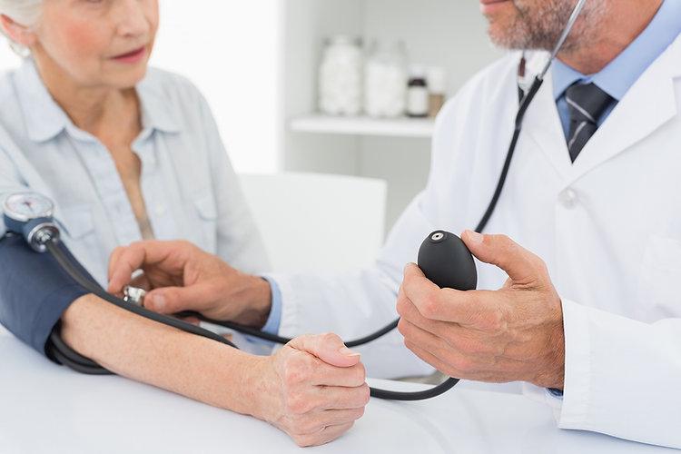 Doctor taking blood pressure of older patient