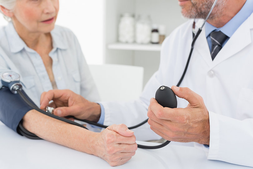 Doctor taking blood pressure of older patient
