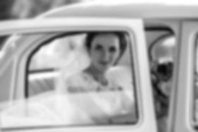 Bride in vintage wedding getaway car