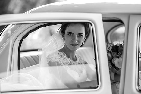 Bride in vintage wedding getaway car