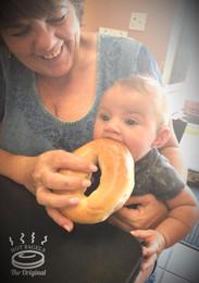 Baby eating bagel.
